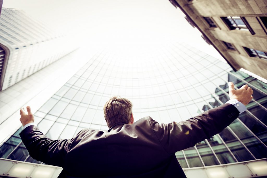 Business man looking up at skyscrapers with arms open