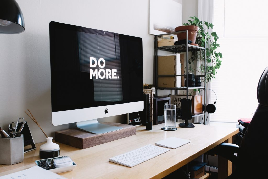 Clean desk with a computer showing Do More on the screen depicting productivity